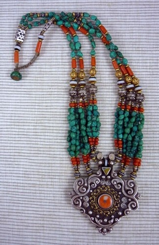 Tibet | Necklace is highlighted by a beautiful antique sterling silver Tibetan pendant. The other ingredients are: antique red coral, antique sterling beads, vermeil beads, dzi agate, old turquoise, and brass.