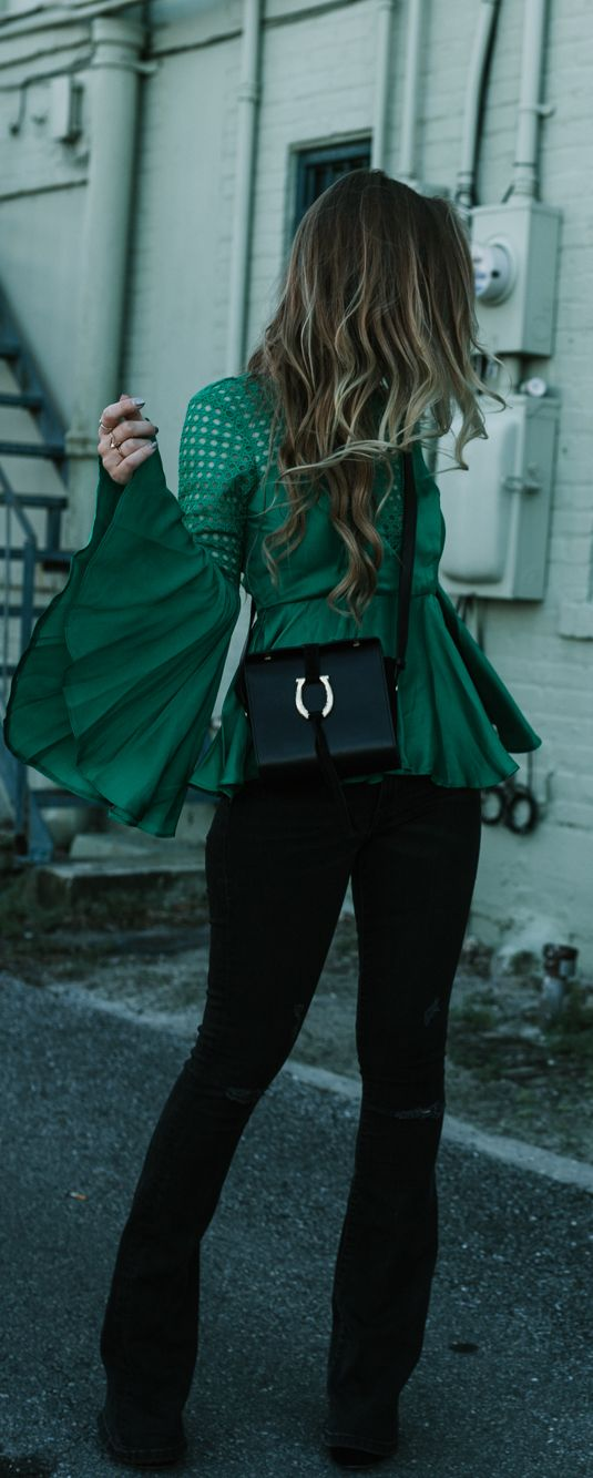 Winter date night outfit styled with satin bell sleeve green top, black flared jeans, and black and gold crossbody