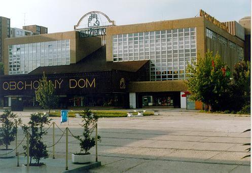 """Obchodný dom Ružinov - v histórii slovenskej architekúry prvá ucelená pomo stavba (""""prístup tvorcov obchodného domu bol dotiahnutý do najmenších detailov – až po značku obchodného domu, grafický dizajn informačného systému a baliaci papier, to všetko od akademického maliara Igora Meluzína"""")"""