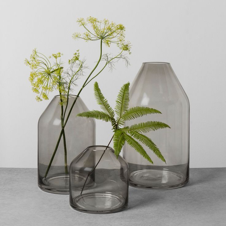 Bring some simple and traditional decor into your home with this Smoke Glass Jug Vase from Hearth & Hand™ with Magnolia. This smoke glass vase features a cylindrical design with a tapered top that ends in a small opening — perfect for a few stems of flowers or decorative filler. This tabletop glass vase can be styled on your dining room table, kitchen counter or coffee table with your favorite filler or flower to create a warm and inviting atmosphere in your home.<br...