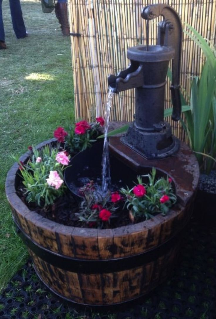 Hand water pump water feature above wine barrel in a garden in Yorkshire. Image from waterfeatures-co-uk