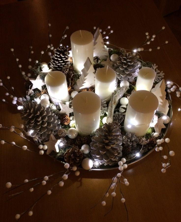Dans une toute autre ambiance, voici un centre de table réalisé avec des bougies, des pommes de pin, quelques branches et surtout une guirlandes lumineuses pour donner l'aspect féerique