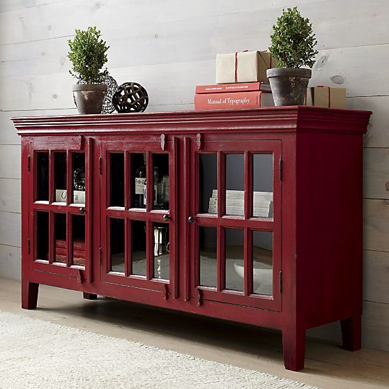 With all the warmth and rustic charm of a one-of-a-kind antique, the rich waxed patina of this red storage cabinet adds instant character to any room. Crafted of shesham and mango wood with traditional tongue-and-groove joinery, the cabinet is topped with architectural crown molding. Three glass-paned doors display everything from books, media equipment and curios to dishes and kitchen collectibles. Hinges and knobs are hand-forged iron; wood hasp closures secure the doors.