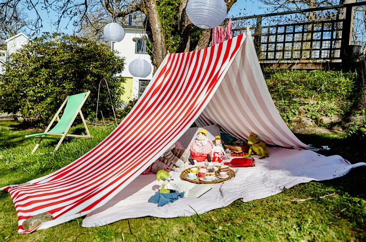 Want to get the kid's outside more? We used a length of fabric to make this cosy tent. Just hang it over a piece of rope and add soft toys and blankets
