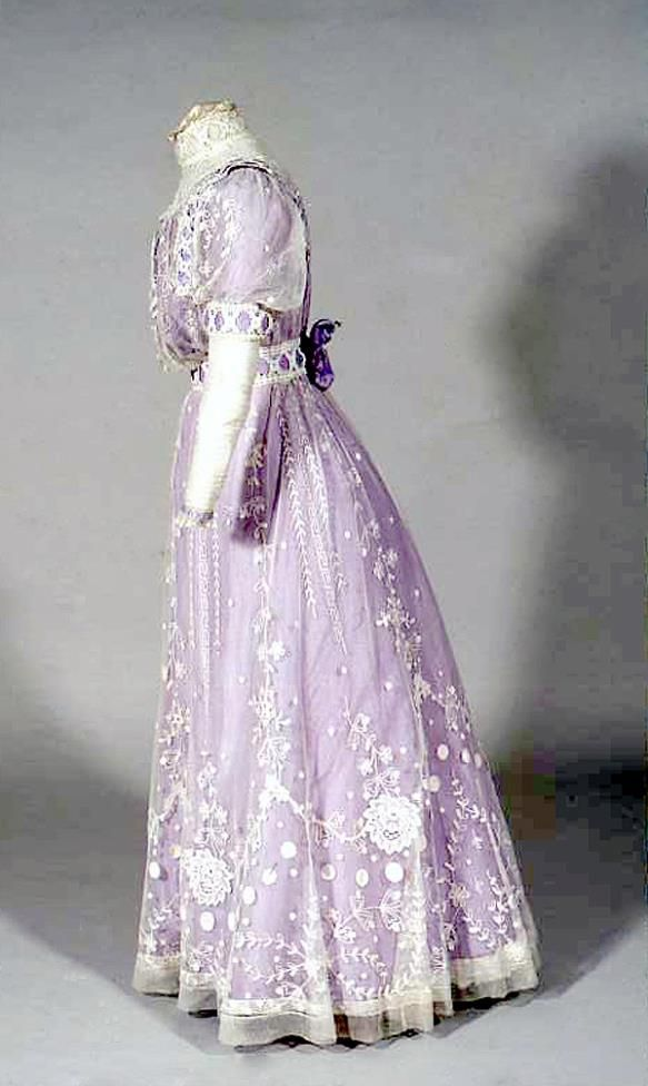Mauve silk dress with overdress of rather coarse tambour or carrick in a cross. Lace finished with borders and motives. Mark: W. Perry, The Louvre, Alnwick, Purveyor of the Royal Family. Worn at investiture of Prince of Wales (Edward VIII) at Carnaervon 1911.