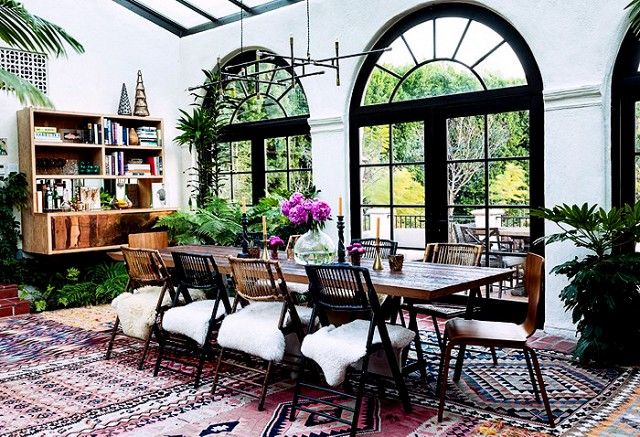 Eclectic dining room with layered rugs, arched windows, and sheepskin seats