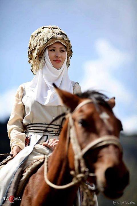 Kırfız Türk Katunu at üstünde, ulusal giysisi ve başlığıyla...