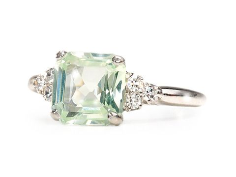 Green Goddess: Spinel Diamond Ring. Seldom seen pale yellow green spinel, 8 mm x 8mm, wst 2.25 carat flanked by 3 single cut diamonds on each side with a total est. weight of .10 carats. 14k white gold, modern estate