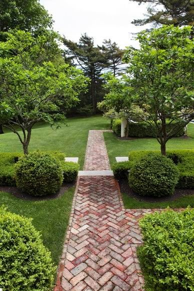 Herringbone brick path between symetrical forms. Trees and Boxwood flank both sides for balance.