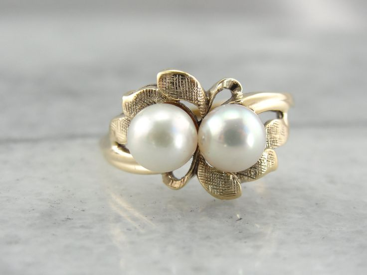 This fun ring is very natural looking, each fully formed petal is etched to a soft texture, creating natural looking shadows in the three dimensional flower petals. Creamy, soft pink and white pearls sit at the center, framed in the bed of petals!  Metal: 10K Yellow Gold Gem: Pink Pearl, White Peal Gem Measurements: 5.8 mm, Round Ring Size: 6.75 Marks: 10KPSCo Stamped on the inside band  SKU #: X5KXQN-P  Each piece has been identified and graded by a Graduate Gemologist who has been…