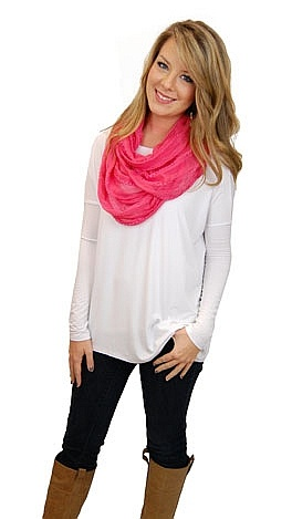 White long sleeved top, black leggings, riding boots and pink infinity scarf.