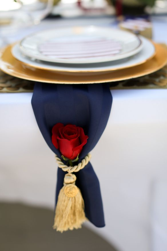 Red, white and blue military wedding place setting. Navy napkin with red rose and gold tassle featuring gold button from Marine uniform. Gold charger plate and US Navy china. Photo by @melissamcclure As seen in @SDSWCreative Planning and design by Stephanie Rose Events
