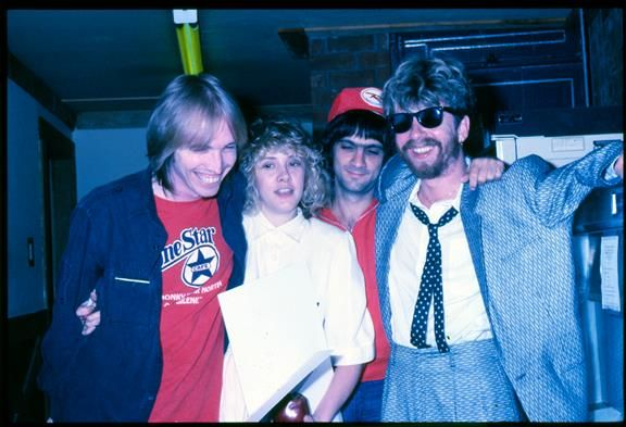 Tom Petty, little Stevie ~ ☆♥❤♥☆ ~ Jimmy Iovine in the background and Dave Stewart with wild hair, wearing sunnies and a bright blue patterened suit