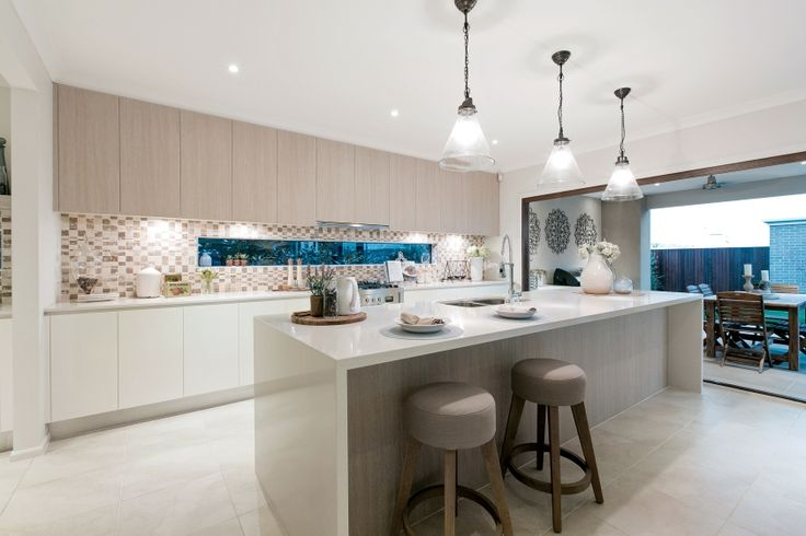 This coastal inspired kitchen stems from a classic base palette of sandy browns. The over sized pendant lamps create a focal point as does the summer- toned tiled splashback. Clean lines throughout keep the look modern.