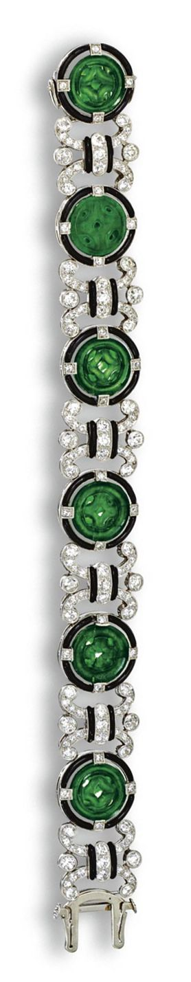 JADE, DIAMOND AND ENAMEL BRACELET, CIRCA 1925. Comprising 6 circular openwork carved jade disks within frames of black enamel set at intervals with small single-cut diamonds, connected by ornate links set with numerous old European-cut and single-cut diamonds, decorated with bands of black enamel, the total diamond weight approximately 6.00 carats, mounted in platinum