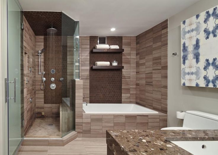 Large-scale tiles mingle with dynamic mosaic glass tile accents, turning this spacious contemporary bathroom into a spa-like retreat. Glass separates the shower and bathtub, allowing the space to feel open while soothing colors, textures and finishes – including the handheld shower fixture and rain showerhead – create a space built for ultimate relaxation. Floating shelves above the bathtub are perfect for storing extra towels for guests.