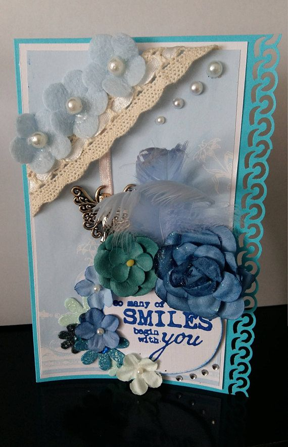 Light blue handmade card with flowers feathers and a fairy.