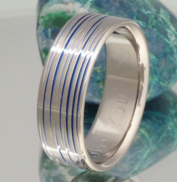 You are one-of-a-kind and deserve this striking Blue Titanium ring hand-striped by our artisans. No two of these exotic tiger style rings are the same. Shown in 7.5mm width and flat profile with blue striping, this ring is also available without color or with diamonds. Wear this ring and keep one paw in the jungle.