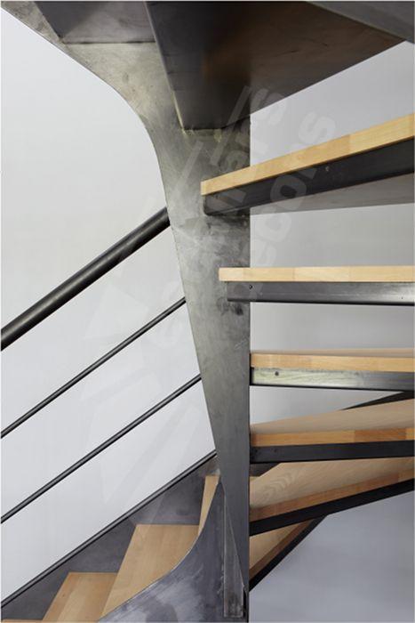 DT103 - ESCA'DROIT® 2 Quartiers Tournants. Escalier métal et bois d'intérieur au design contemporain. Marches balancées type caisson et plateaux bois massif pour une décoration moderne et chaleureuse. Rampe contemporaine composée d'une main courante tube ergonomique et de lisses parallèles fines en fer rond. Limons en tôle plane avec découpe géométrique suivant le balancement des marches. Finition : acier brut patiné. - © Photo : Nicolas GRANDMAISON