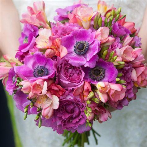 La novia lleva un arreglo de flores tropicales, incluyendo anémonas púrpuras vivos