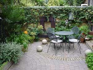 Small courtyard patio with vines growing on the walls and table and chairs  in the middle