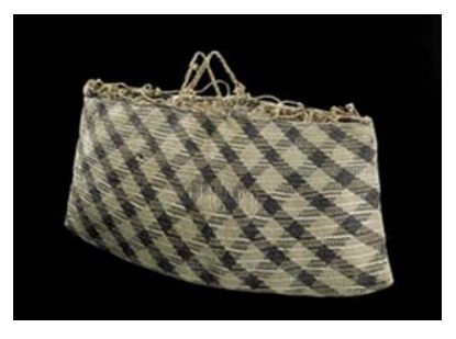 This kete (basket) is made from finely-woven harakeke (flax). It has an open pattern of black and brown–yellow colours.