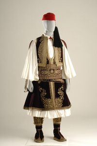 Otto, the first king of Greece established this urban costume as the formal Court attire in around 1835. Originally the uniform of the Greek Revolutionary chieftains, it is characterized by the long (below-the-knee) foustanella, and the silk tourbani that was usually wrapped and tied around the fez. The ornately embroidered gold selahi (wide belt that held weapons) was worn on top of a red silk sash. The costume had three jackets: the yileki (waistcoat) worn underneath, the fermeli with…