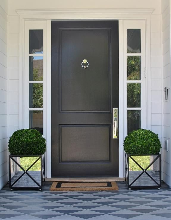 Mirrored planters flank a welcome mat placed in front of a black front door accented with a nickel ring knocker and positioned between side lights framed by white siding.