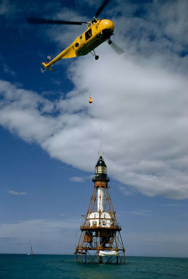 Picture of a Coast Guard helicopter dropping mail over a lighthouse at sea.
