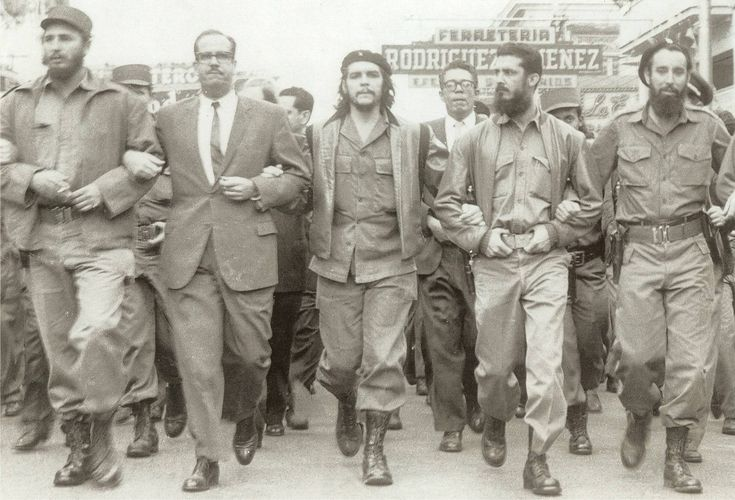 Fidel Castro, Che Guevara, and other leading revolutionaries marching arm in arm, 1960