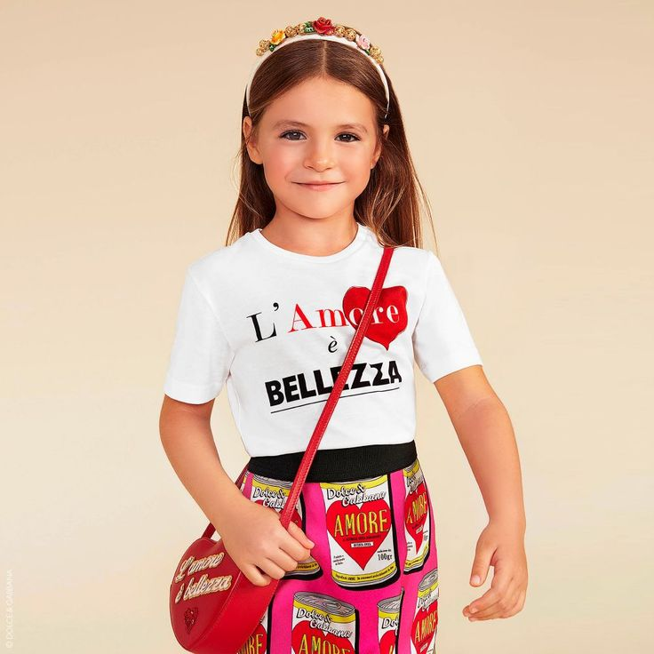 Girls red leather heart-shaped bag from Dolce & Gabbana. Made in Italy with the finest craftsmanship, there is a stitched 'Love & Beauty' slogan in gold and pink on the side, with a red sequin heart. The shoulder strap is adjustable, with a zip fastening across the top.