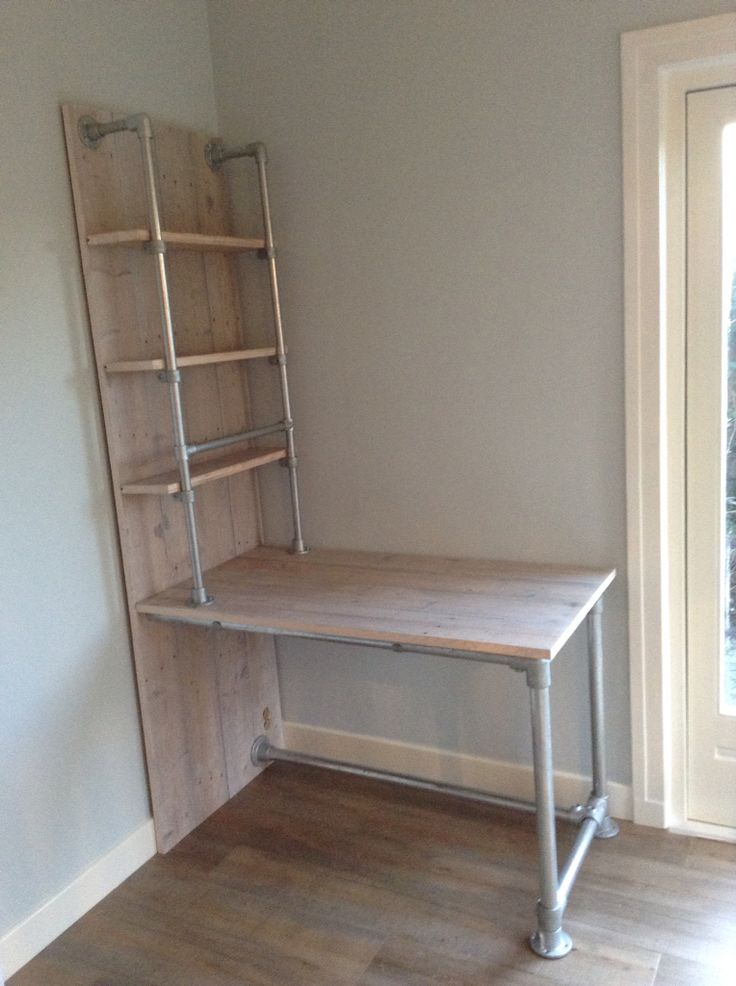 Custom made desk with integrated shelves. Built using tube and fittings.