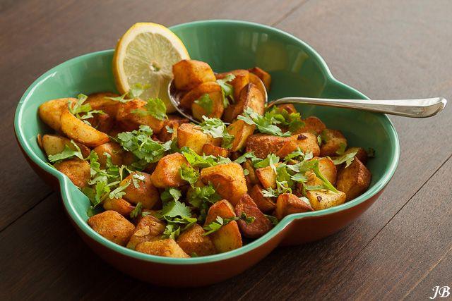 Ingrediënten:- 1 kilo aardappels, geschild en in blokjes van 2 cm- 150 ml olijf- of zonnebloemolie- 3 tenen knoflook, in dunne plakjes- zout naar smaak- handvol korianderblaadjes- sap van 1 citroen- 2