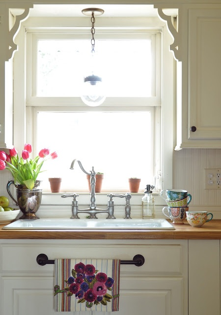 Ikea wood countertops and a vintage style kitchen.. LOVE the faucet, light, cabinets, and little scroll detail