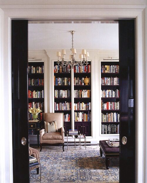 Beautiful floor-to-ceiling shelves filled with books. Very elegant room.