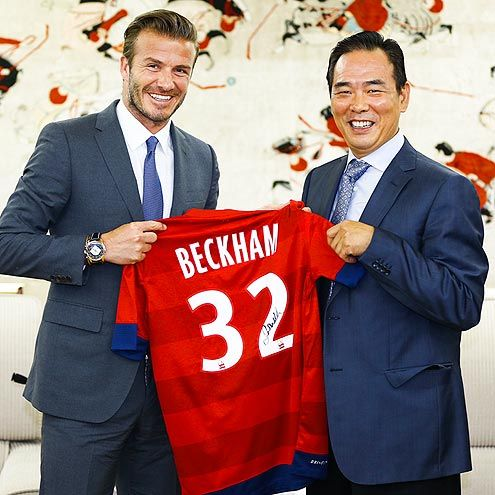 David Beckham hands off a signed jersey to sports administrator Cai Zhenhua Monday at a Beijing, China, ceremony. 6/18/13