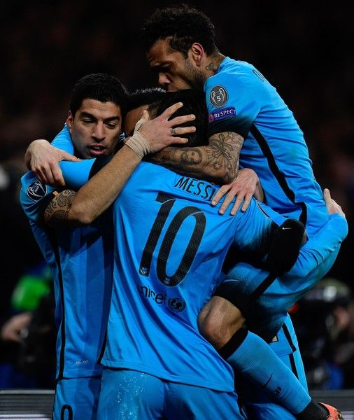 Barcelona's Argentinian forward Lionel Messi (C) celebrates scoring his team's first goal with Barcelona's Uruguayan forward Luis Suarez (L) and Barcelona's Brazilian defender Dani Alves during the UEFA Champions League round of 16 1st leg football match between Arsenal and Barcelona at the Emirates Stadium in London on February 23, 2016.