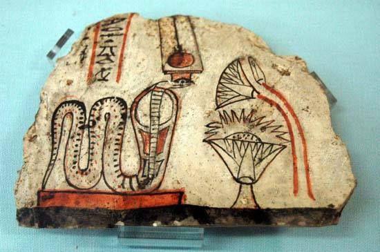 """Ostracón con la adoración de la diosa Meret-Seger, """"La que ama el silencio"""". Esta cobra es la manifestación divina de la montaña tebana (hoy el Qurna). Porta un tocado solar con altas plumas y tiene ante sí una copa y ofrendas de flores de loto. Su nombre está escrito en jeroglíficos con tinta negra.  La pieza proviene del poblado de Deir el-Medina y se expone en el Museo Egipcio de Turín, Italia."""