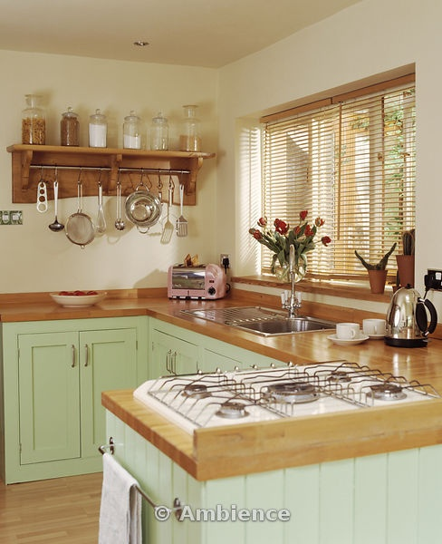 Gas hob in wooden worktop on peninsular unit in pastel green cottage kitchen with slatted wood blind