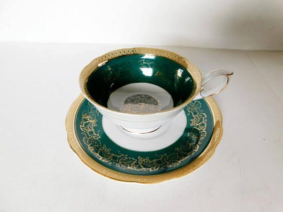"Handpainted cup and saucer in a gold vine on green band design, gold accenting  The cup is 2"" (5.1 cm) high x 3 3/4"" (9.5 cm) at the brim and the saucer is 5 1/2"" (14 cm) in diameter  This set is in very good condition and only appears to have seen use as a collectible  Made of china from Occupied Japan by Shafford    These items have no nicks, chips, cracks, or signs of repair 
