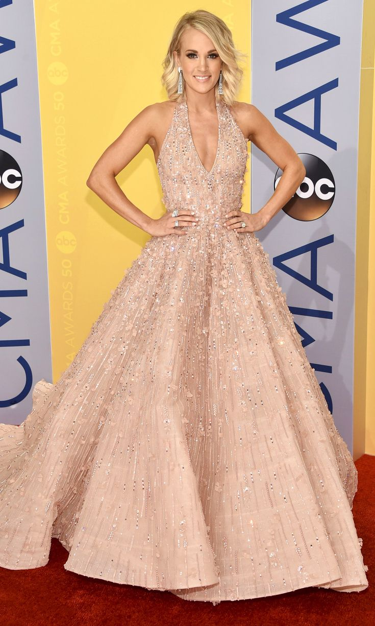 CARRIE UNDERWOOD looks like the belle of the CMA ball in a heavily beaded blush Michael Cinco gown, which she describes as girly, princessy and pretty, plus major Butani earrings and a handful of Hearts on Fire and Harry Kotlar rings to finish out her bling.