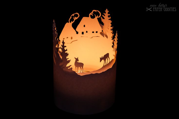 Construction paper for a little tea light lantern. Two layers, showing a snowy mountain village and deer.