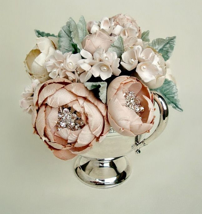 Mini table arrangement that is the perfect accessory for a desk or bedside table. Imagine this as a birthday or Mother's Day gift. Please contact me to purchase this listing.Each one is placed in a carefully chosen container. More of these to come and each one is uniqueThis silk fabric bouquet is comprised of hand cut and formed silk fabric flowers of various shades of blush and ivory. Each open flower has its own hand placed highlights of rhinestones. Completely handmad...