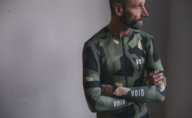 Performance Fit — Tailored for a relaxed fit and upright riding position. Size down for a tighter, more aerodynamic fit.  This high performance jersey takes hints from the Swedish fashion scene and is made to spice up your cycling wardrobe. The M90 pattern is a geometric camouflage made to feel at home in our temperate forests. The VOID heritage stripes at the inner zipper placket are a nod to our Scandinavian design legacy.  The jersey comes in a high quality, European made, lightweight…