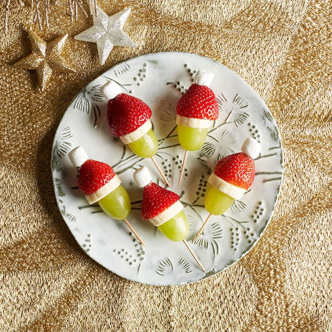 "Your little helpers will love these. These fruity and festive bites will have your guests singing ""All I Want for Christmas Is Fruit!"" What You'll Need: Mini marshmallows Strawberries Bananas Green grapes Toothpicks What to Do: Cut the tops off your strawberries and chop your bananas into thin slices. Slide a grape, banana slice, and...Read More »"