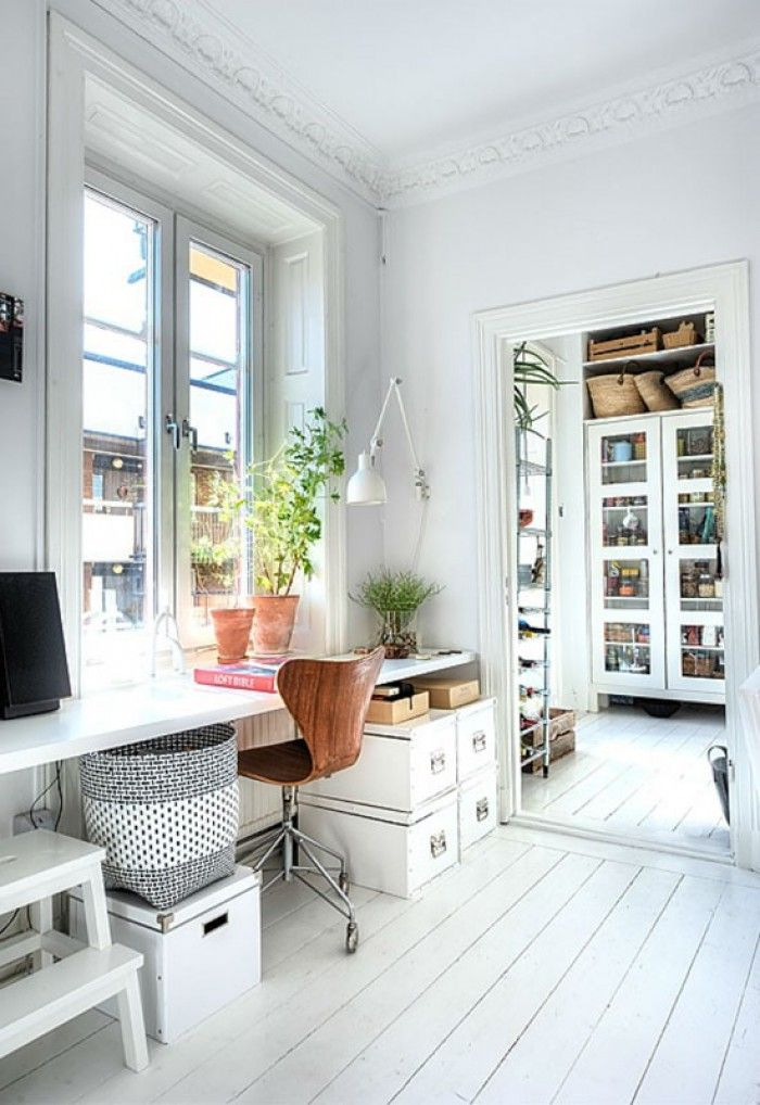 This all white home office is the perfect apartment office. It is not too big and has all the essentials from lighting to storage. It is perfect for a young couple's apartment or a single woman living in the city.