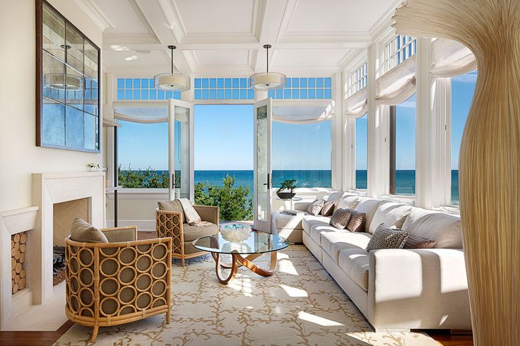 Bright Living Room With Deluxe Sofa And Rattan Armchairs Also Round Glass Table Along With Fireplace And Hanging Lamps Decorated By Fantastic Beach Over The Windows Curved Architecture of the Big House On The Beach Home design