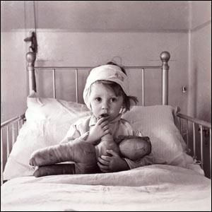1940s vintage exhibition print of a Cecil Beaton photograph MH 26395. Eileen Dunne, aged three, sits in bed with her doll at Great Ormond Street Hospital for Sick Children, after being injured during an air raid on London in September 1940.