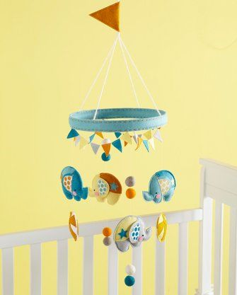 Decorate a nursery by dangling fun felt balls and elephants with polka dot ears beneath a big top.