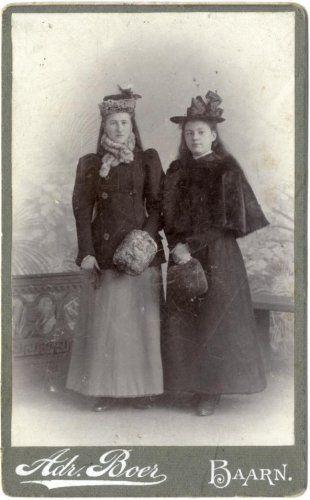 Adriaan Boer | Studiofotografie, Carte de visite. Portret van twee meisjes in winterkleding. De meisjes zijn geportretteerd voor een decor met een stenen hekwerk en planten. Het meisje links draagt een jasje en een bonten sjaal. Het meisje rechts draagt een bonten cape. Beiden hebben een bonten mof en sierlijke hoeden. Nederland, Baarn, 1897-1912.